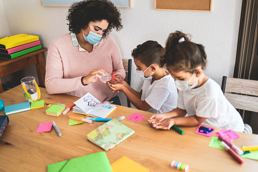 Teacher disinfect students hands with sanitizer gel - Back to school and covid-19 lifestyle concept - Main focus on woman's cardigan