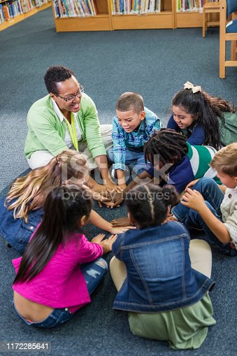 A female African-American teacher sitting on the floor in a circle with her elementary school class, a group of seven multi-ethnic children. They are playing a game, reaching, putting their hands in the middle of the circle.