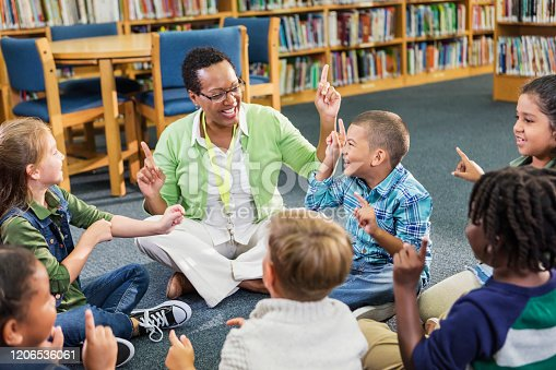 A female African-American teacher sitting on the floor in a circle with her elementary school class, a group of seven multi-ethnic children. They are playing a game, pointing their fingers up in the air.