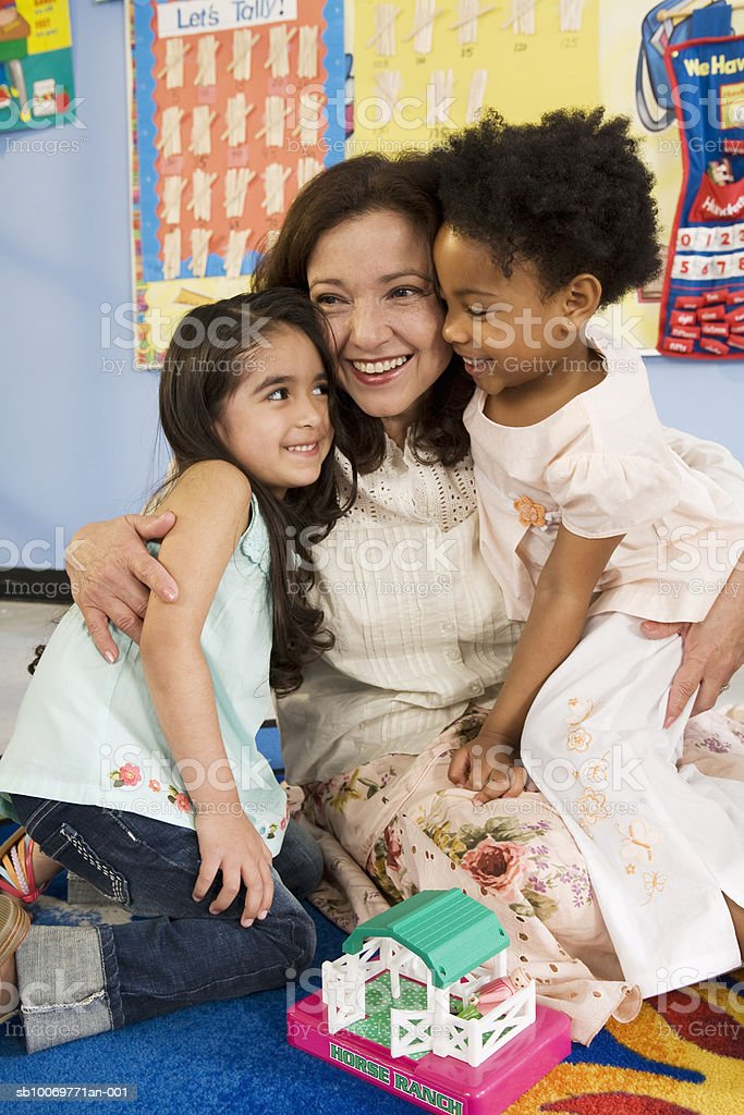 Teacher embracing girls (4-5), smiling royalty-free stock photo
