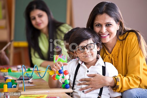 Happy teacher embracing preschool student