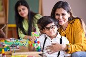 Happy teacher embracing preschool student
