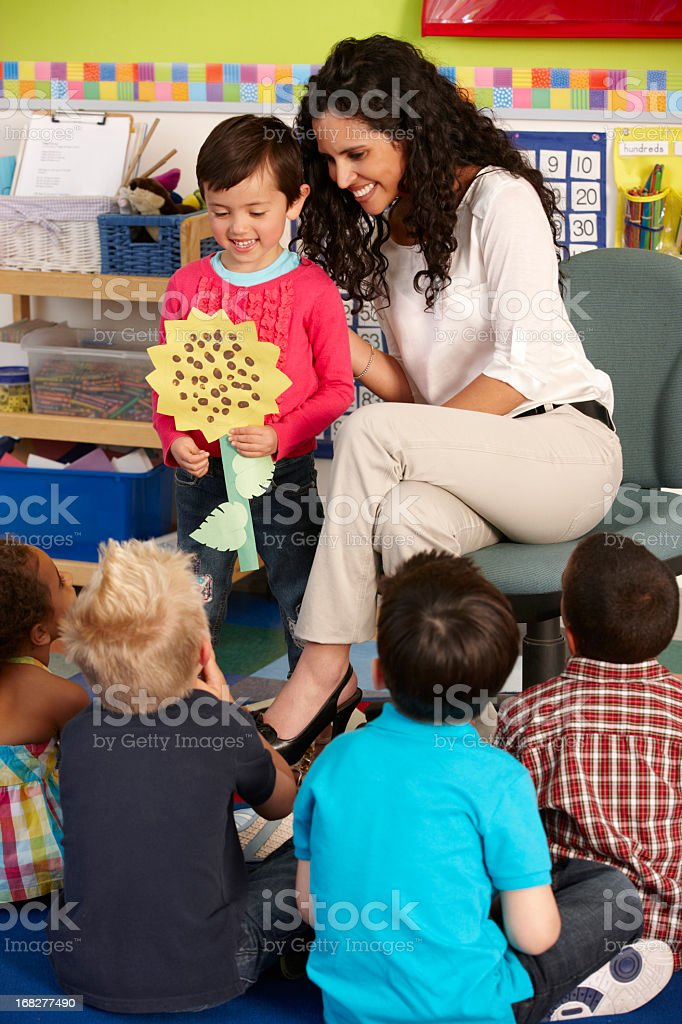 Teacher encourages a young student presenting during class royalty-free stock photo