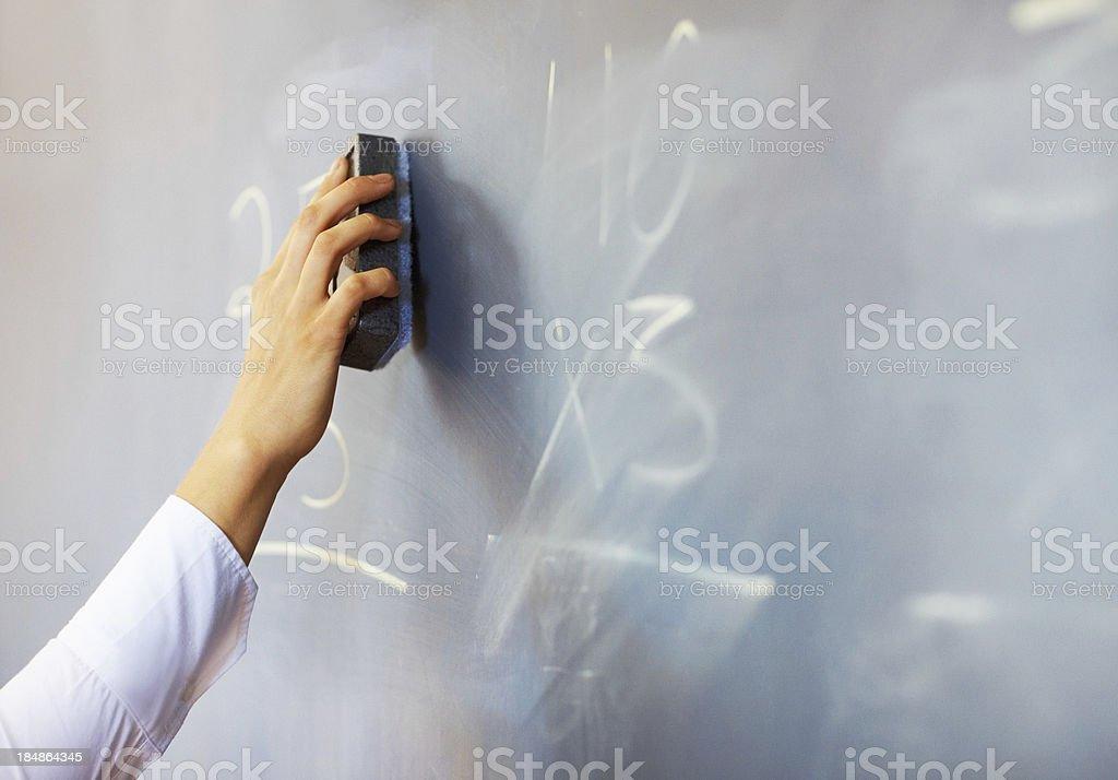 Teacher erasing chalkboard stock photo