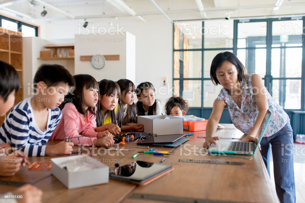 Teacher explaining a project to a group of young students. Okayama,...