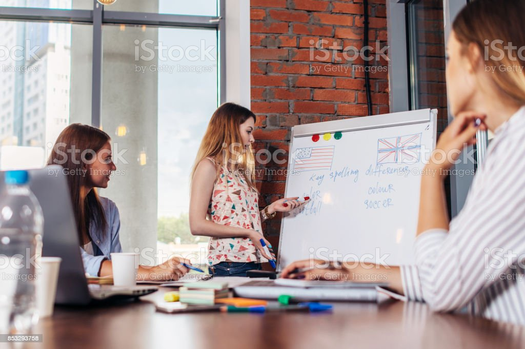 Teacher explaining differences between American and British spelling writing on whiteboard while adult students sitting at desk listening to her in stylish English language school stock photo