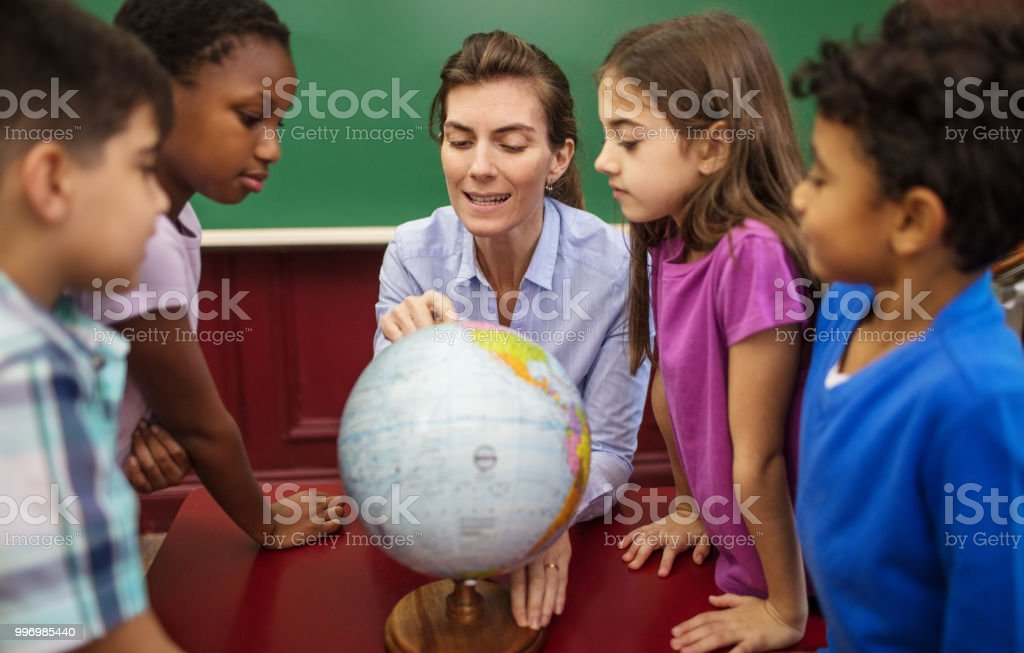 Teacher explaining globe to students in classroom stock photo
