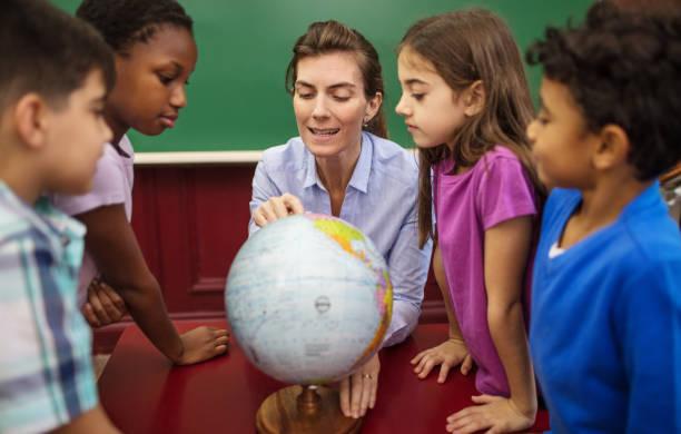 Teacher explaining globe to students in classroom stock photo