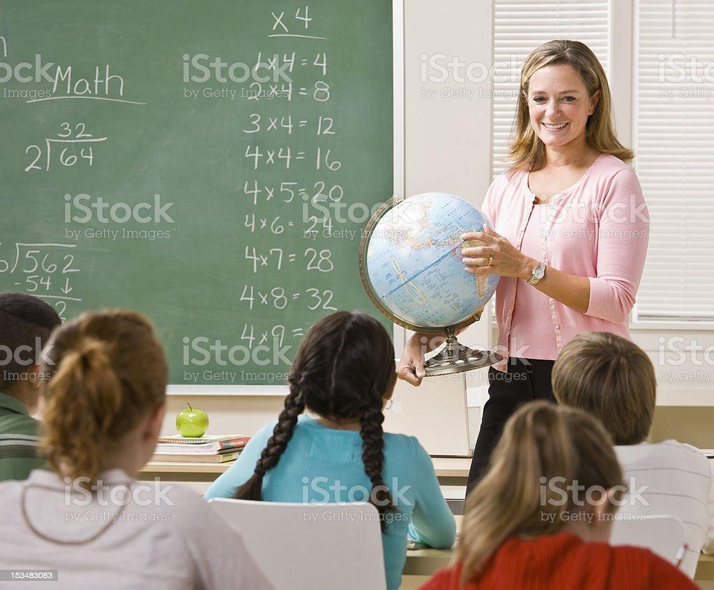 Teacher Explaining Globe to Students royalty-free stock photo