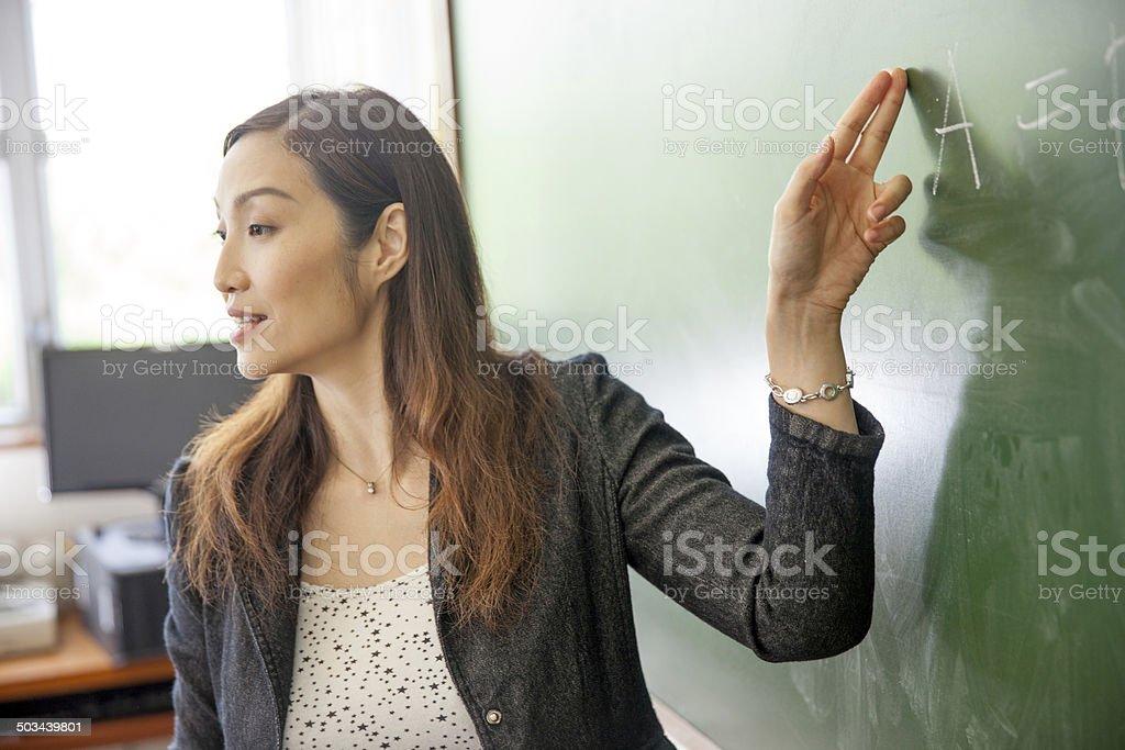 Teacher explaining the economic equation圖像檔