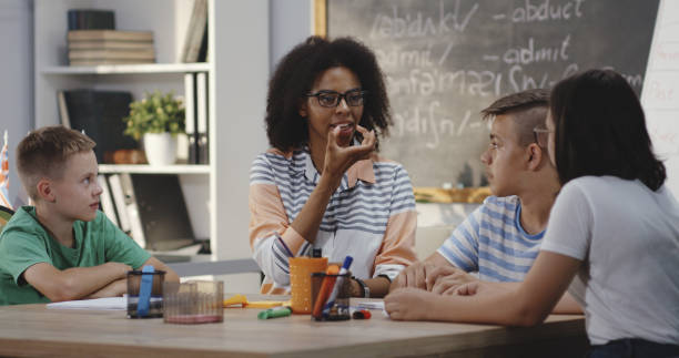 Teacher explaining to pupils in a classroom Medium shot of speech therapist explaining to pupils in a classroom medium shot stock pictures, royalty-free photos & images