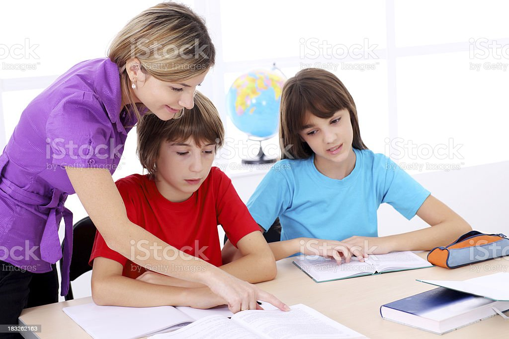 Teacher explaining to schoolboy the task in classroom. royalty-free stock photo