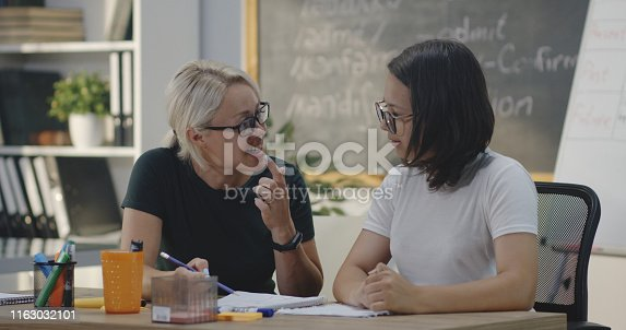 Medium shot of teacher explaining to student in a classroom