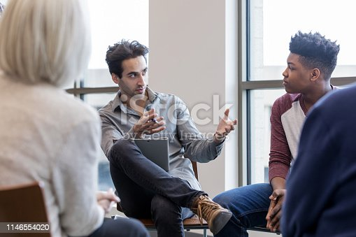 After a fight at school the mature adult female principal and mid adult teacher meet with a student to explain the consequences of his actions.