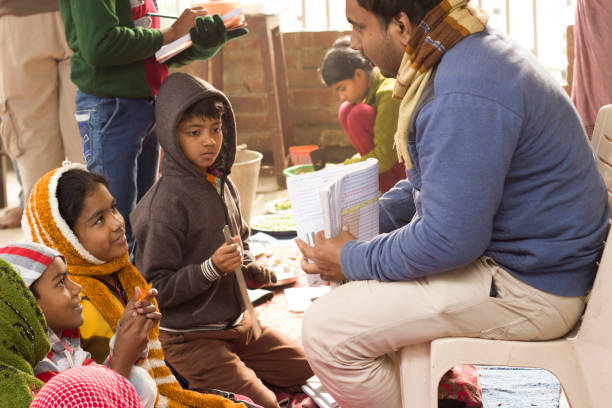 Teacher explains to students, holding exercise book. In a village in Bengal, India developing countries stock pictures, royalty-free photos & images
