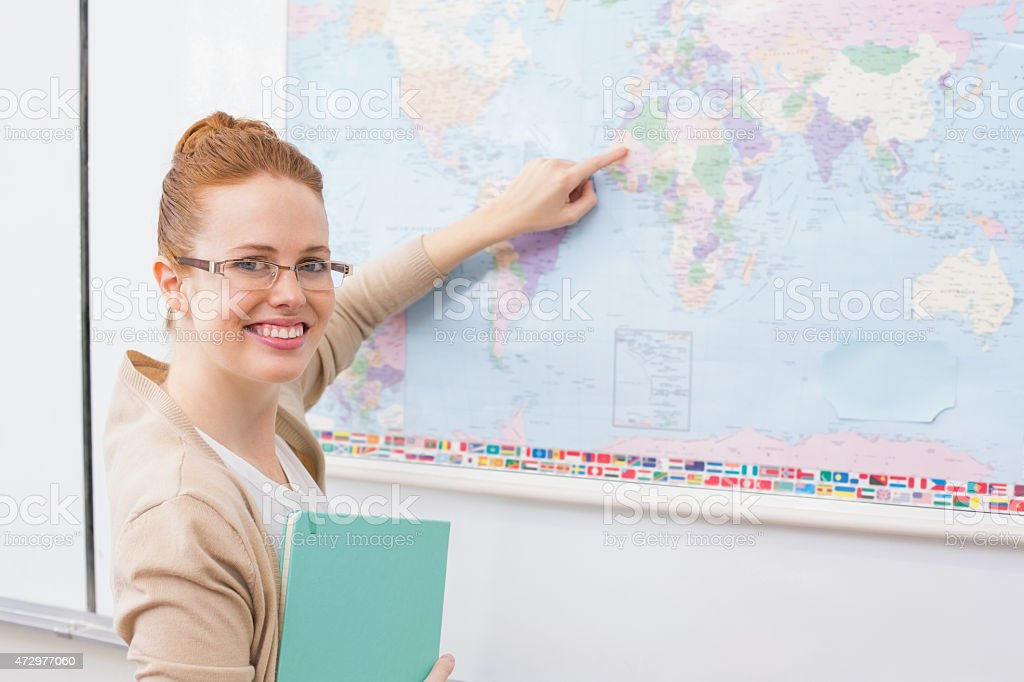 Teacher giving a geography lesson in classroom stock photo