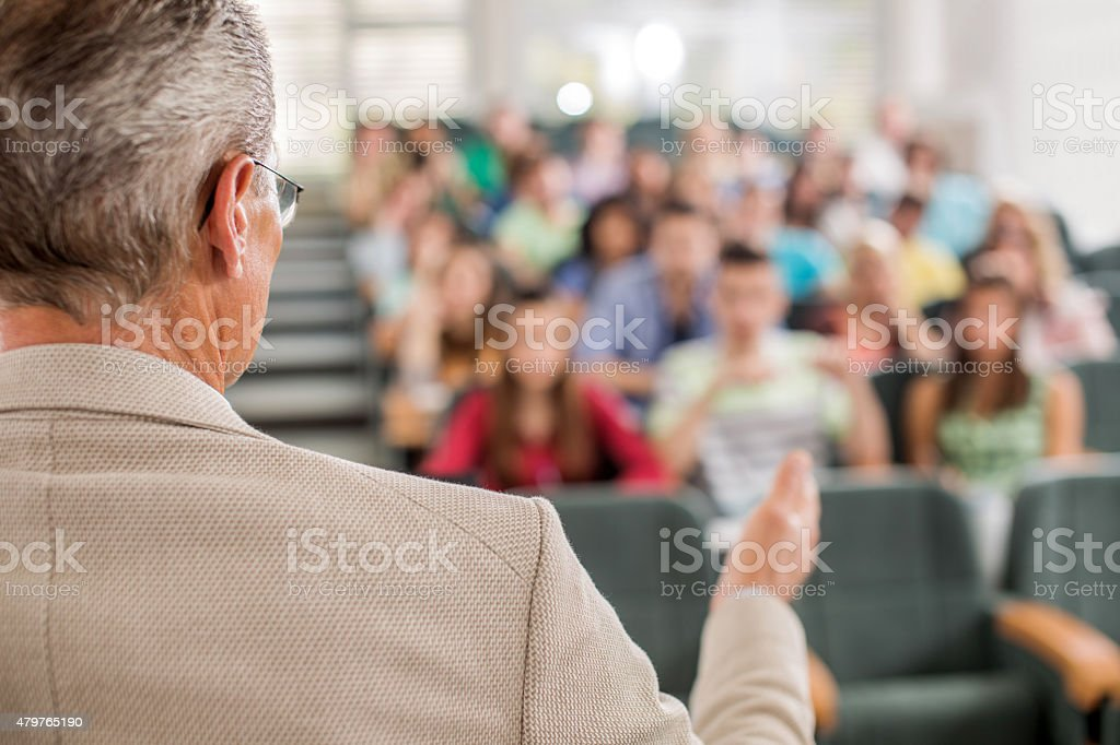 Teacher giving a lecture in amphitheatre. stock photo