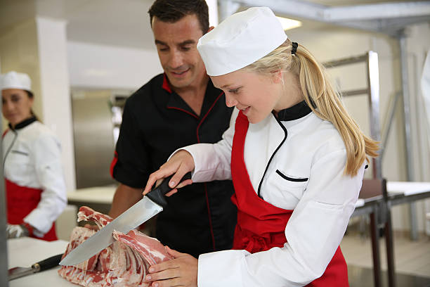 Teacher giving a lesson of cutting meat stock photo
