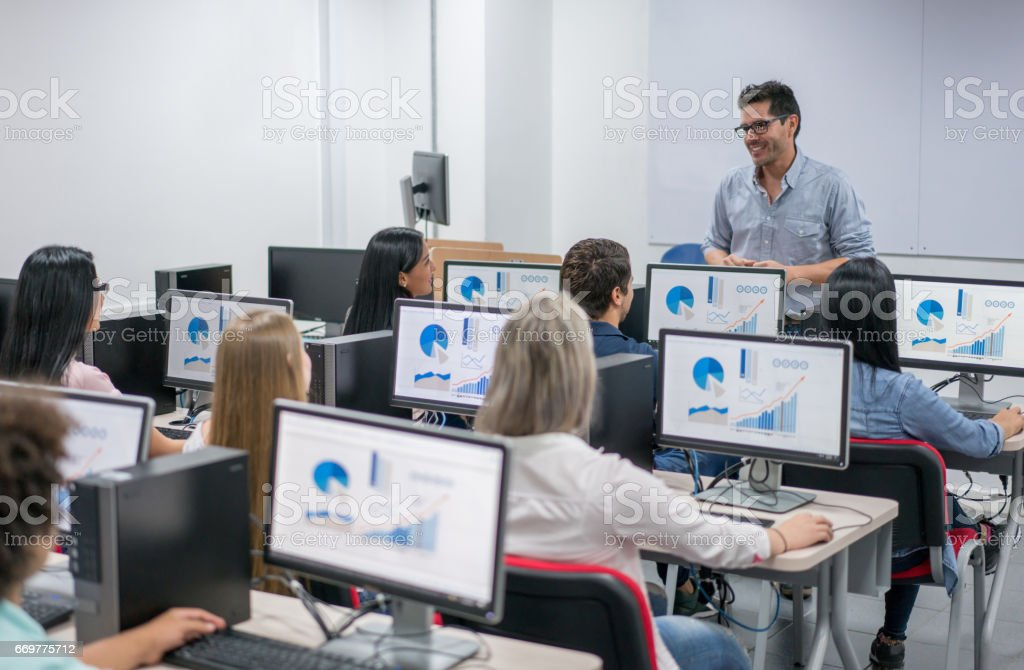 Teacher giving an IT class at school to a group of students stock photo
