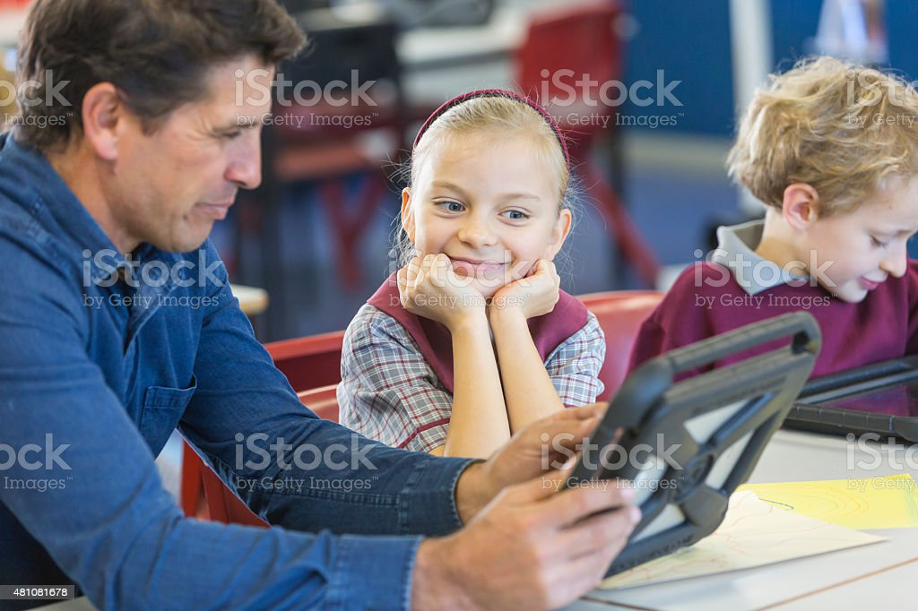 Teacher Giving Lesson Using a Tablet Computer in the Classroom stock photo