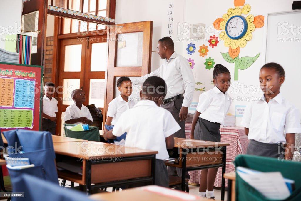Profesor saluda a los niños llegar al aula de la escuela primaria - foto de stock