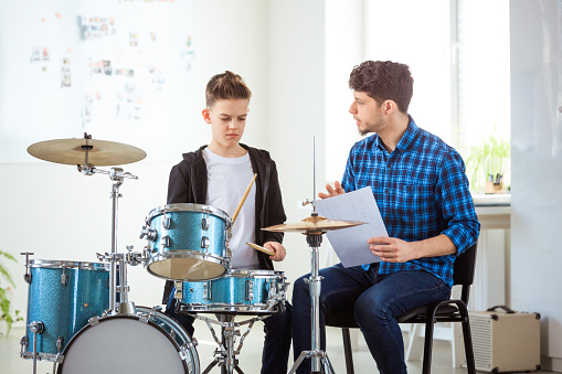 Teacher Guiding Boy With Sheet While Playing Drums Stock Photo - Download Image Now
