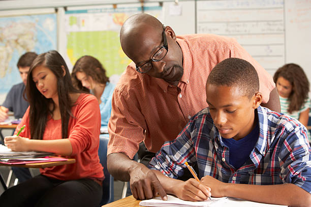 Teacher helping a male pupil studying at a desk in classroom stock photo