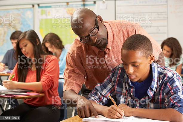 Teacher Helping A Male Pupil Studying At A Desk In Classroom Stock Photo - Download Image Now