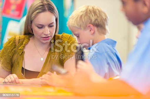 istock Teacher helping a student in class. 909313776