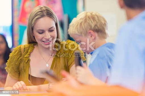 istock Teacher helping a student in class. 909313778
