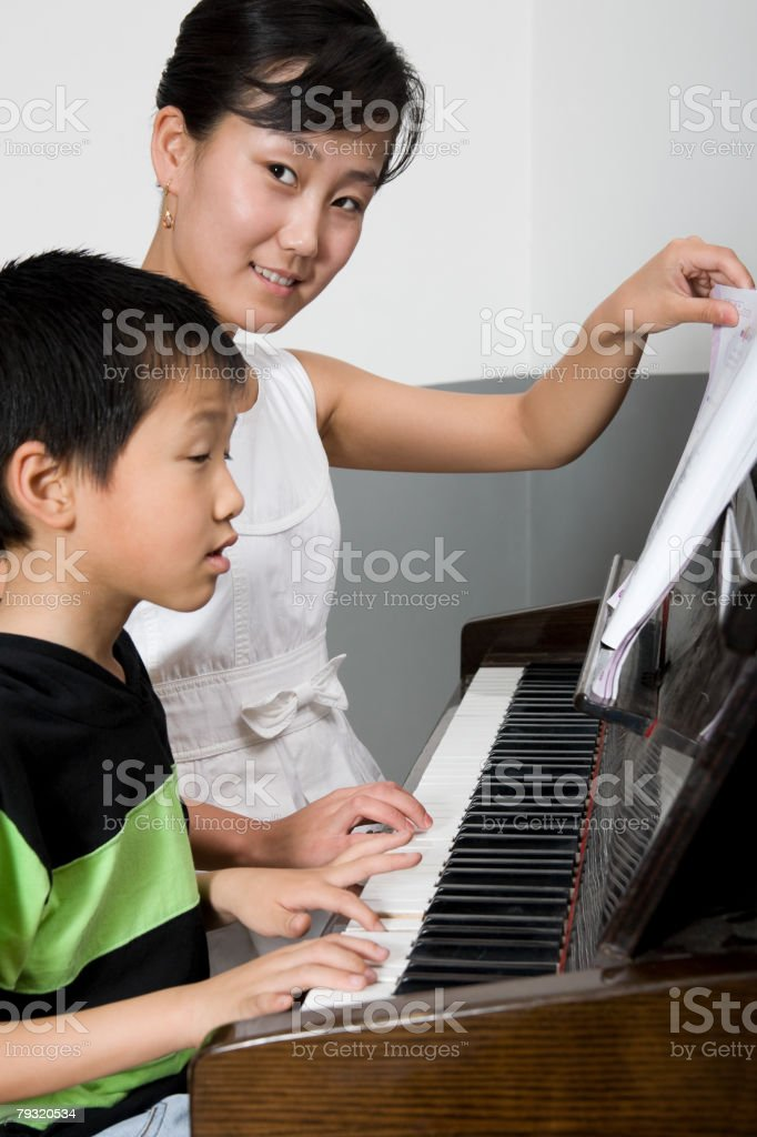 A teacher helping a student play the piano royalty-free 스톡 사진
