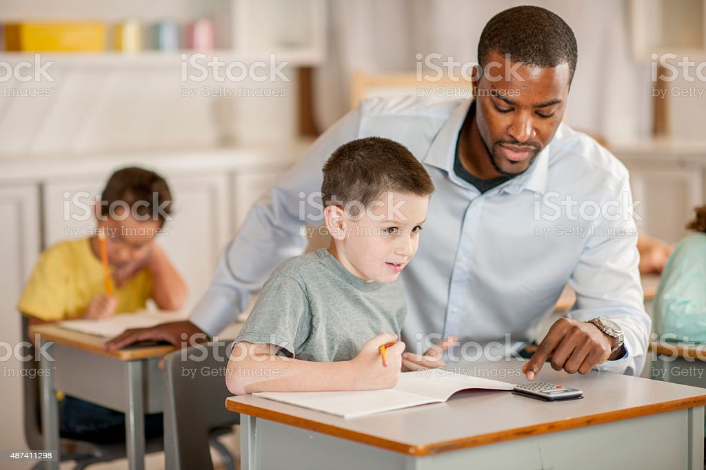 Teacher Helping a Student with Math stock photo