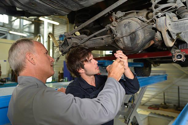Teacher helping a trainee in car repair shop stock photo