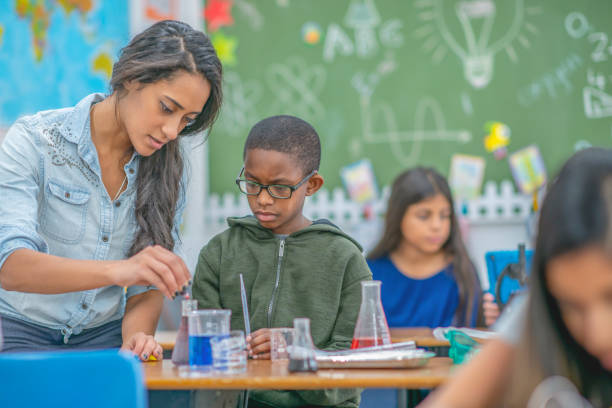 teacher helping a young boy with chemistry - middle school teacher stock pictures, royalty-free photos & images