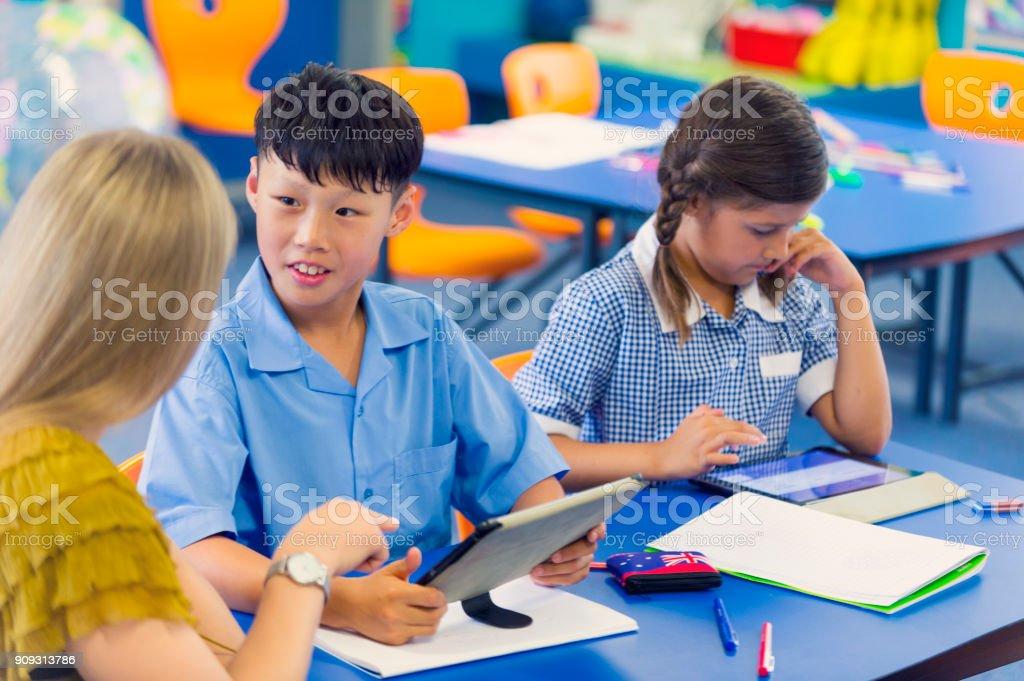 Lehrer helfen, eine asiatische Studentin in der Klasse. – Foto