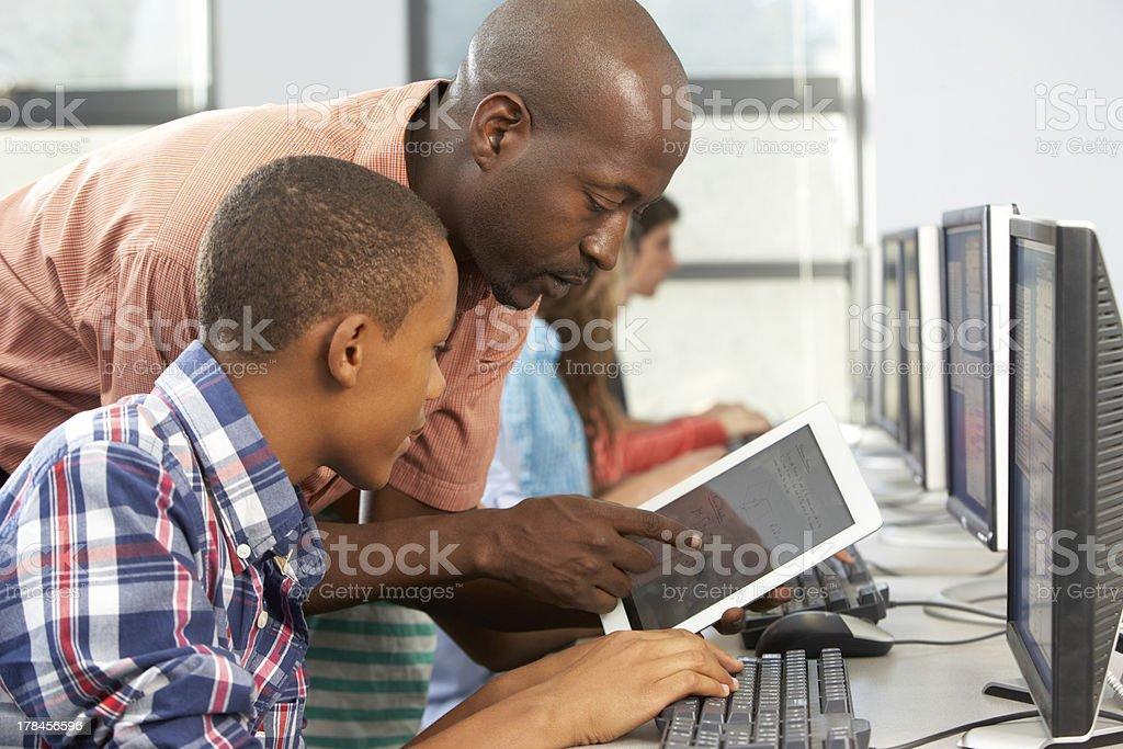 Professor ajudar menino para usar computador Tablet Digital de Classe - foto de acervo