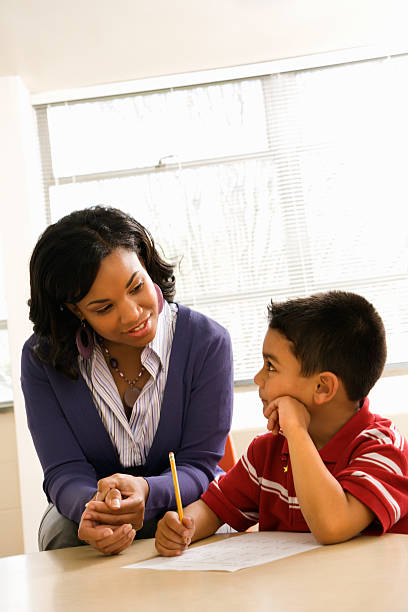 Teacher Helping Boy With Schoolwork stock photo