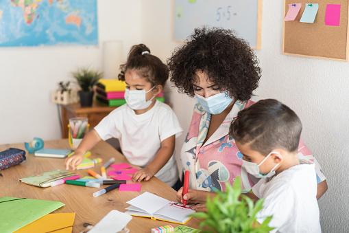 Teacher helping children inside preschool wearing safety masks - Focus on woman face