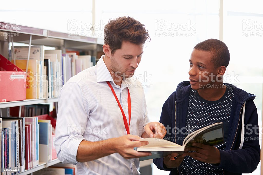 Teacher Helping College Student With Studies In Library stock photo