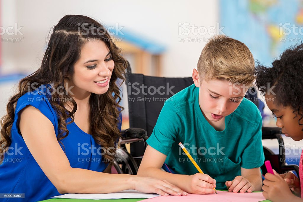 Hispanic female teacher helping an elementary age Caucasian boy in a...