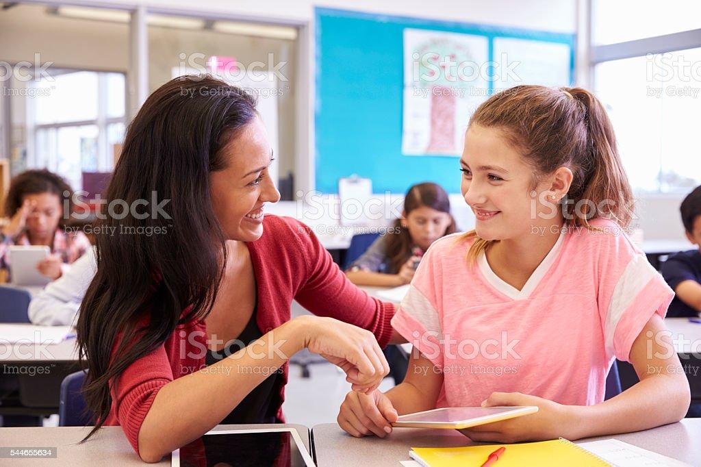 Professor ajudar a escola primária garota usando Tablet computador - foto de acervo