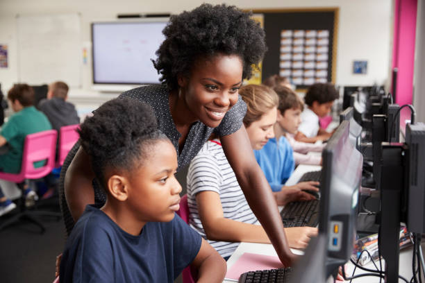 Teacher Helping Female Pupil Line Of High School Students Working at Screens In Computer Class stock photo