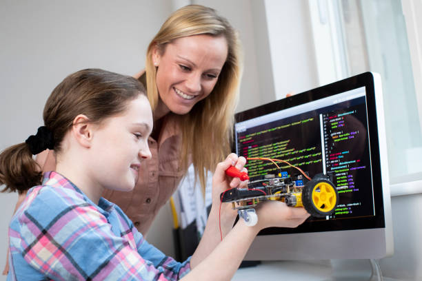 Teacher Helping Female Pupil To Build Robot Car In Science Lesson Teacher Helping Female Pupil To Build Robot Car In Science Lesson middle school teacher stock pictures, royalty-free photos & images