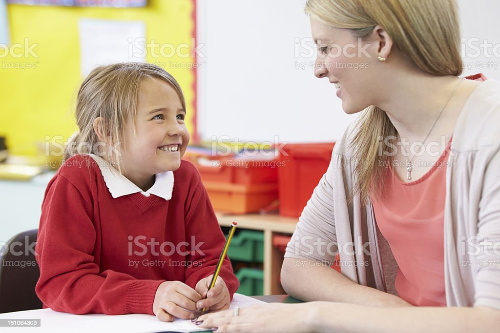 Teacher Helping Female Pupil With Practising Writing At Desk royalty-free stock photo