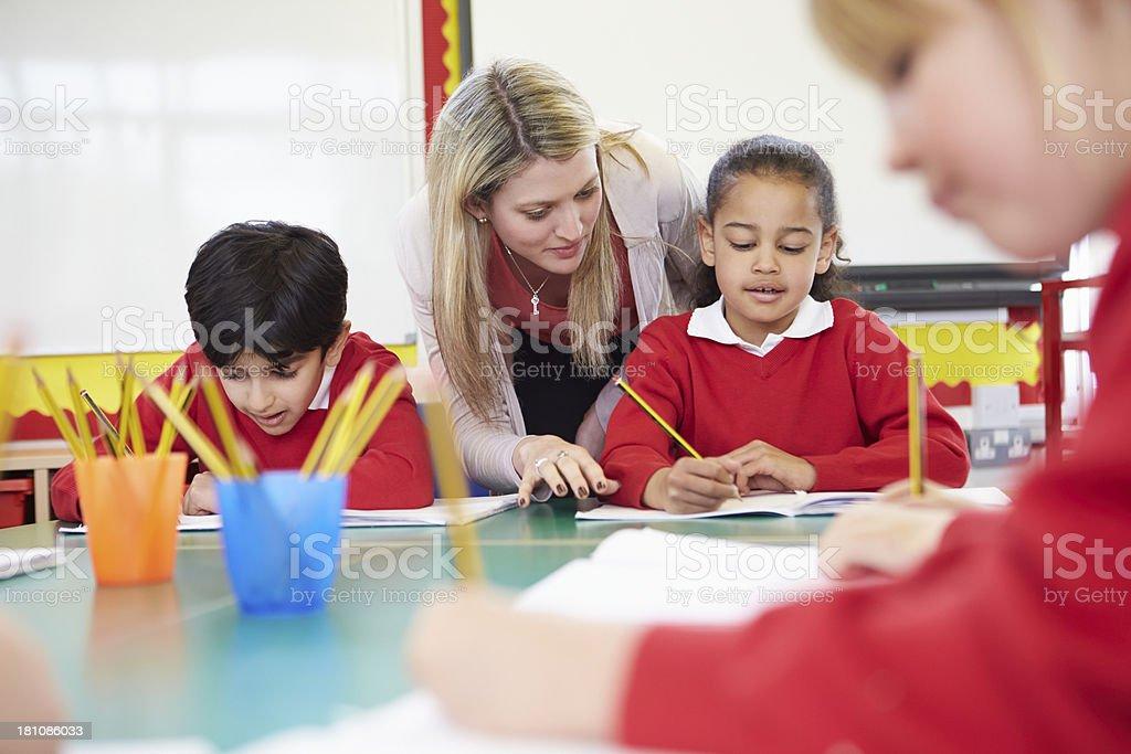 Enseignant aidant femme élève écrire lecture au bureau pour
