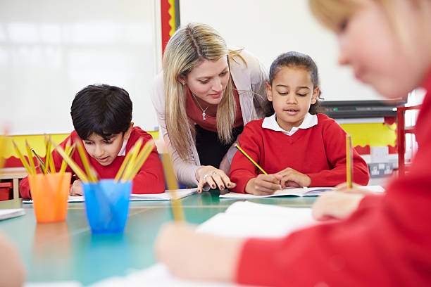 teacher helping female pupil with writing - primary school stock pictures, royalty-free photos & images