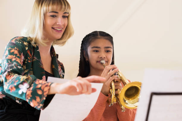 Teacher Helping Female Student To Play Trumpet In Music Lesson Teacher Helping Female Student To Play Trumpet In Music Lesson trumpet stock pictures, royalty-free photos & images
