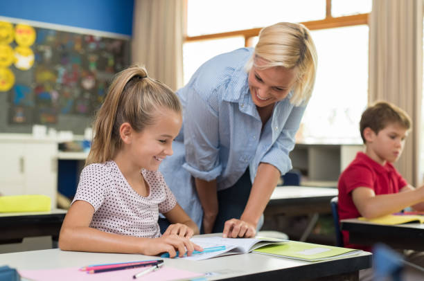 Teacher helping girl to study stock photo
