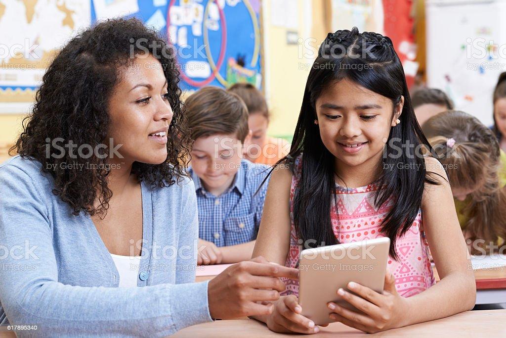 Professor ajudar Grupo de crianças na escola primária em computador - foto de acervo