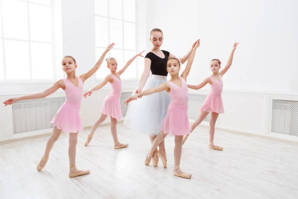 Teacher helping her students during dance class stock photo